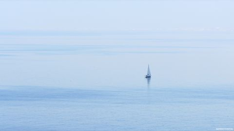 A single sail boat on the wide blue sea.
